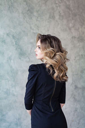 Woman with beautiful healthy curly hairstyle in black dress on gray background portrait