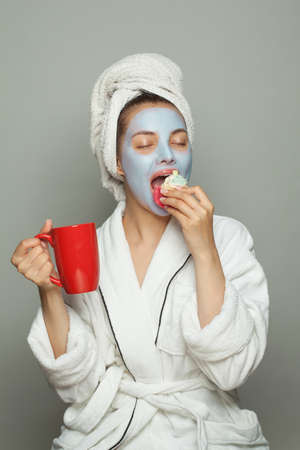 Happy young woman in cosmetic face mask eating breakfast and drinking coffee. Female day routine Banco de Imagens