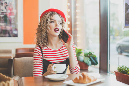 Pretty happy young woman with smartphone in cafe Banco de Imagens
