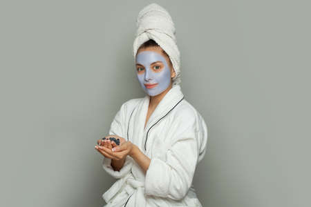 Cute young woman spa model in blue cosmetic face mask holding organic blueberries. Facial treatment and skin care concept Banco de Imagens