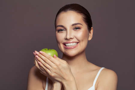 Beautiful smiling woman with green apple on brown background