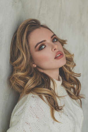 Portrait of nice blonde woman with healthy curly hair and makeup