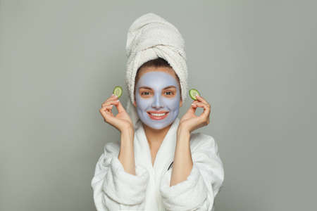 Happy woman in moisturizing cosmetic face mask with green cucumber. Facial treatment and skin care concept