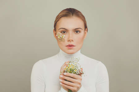 Beautiful emotional woman with flowers. Hope concept