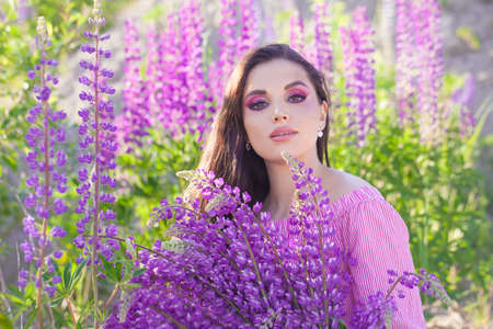 Lovely brunette woman with colorful summer flowers outdoors
