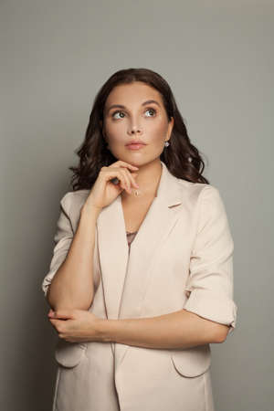 Thinking businesswoman on gray portrait 免版税图像