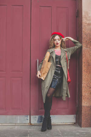 Fashion portrait of perfect young model woman in red french beret standing near red wooden door