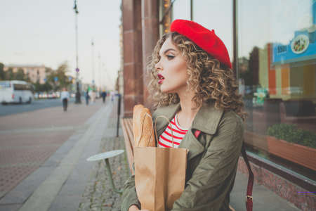 Stylish young woman in red beret holding fresh french baguette in craft paper bag outdoor