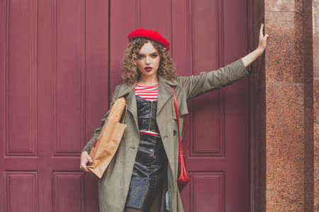 Fashion model woman in red beret laughing against red wooden door 免版税图像