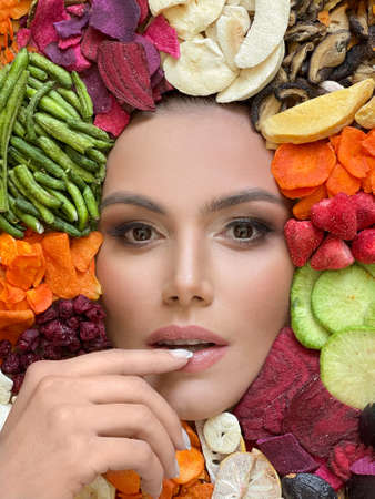 Perfect healthy woman on colorful vivid organic fruits and vegetables chips 免版税图像