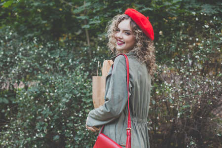 Pretty young woman in red beret holding craft paper bag with fresh french baguette against green leaves