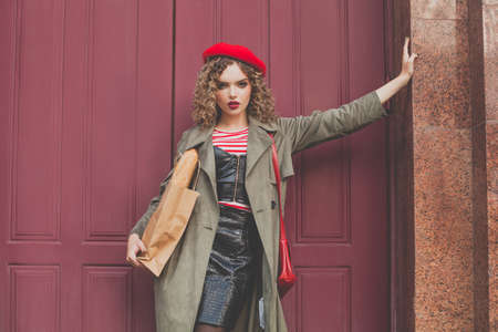 Fashion model woman in red french beret standing near red wooden door