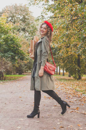 Autumn portrait of happy beautiful woman in red french beret and handbag outdoor
