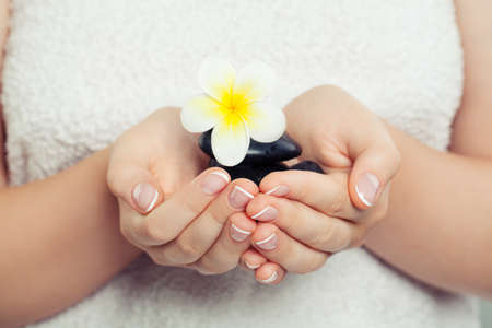 Spa, wellness and ayurveda concept. Female hands with black massage stones and flower 免版税图像