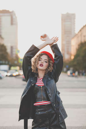 Fashion beauty portrait of stylish woman in black leather jacket and red beret posing on the street