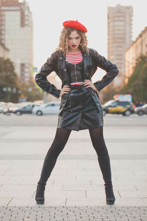 Fashion portrait of young woman in black leather jacket and red beret posing on the street