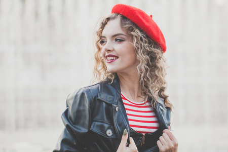 Young woman in red beret smiling, outdoor portrait