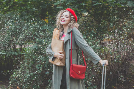 Happy young woman in red french beret and handbag outdoor 免版税图像