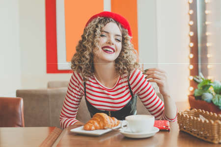Young smiling woman in red beret having a french breakfast with coffee and growing sitting at the cafe