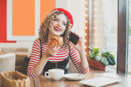 Young woman laughing, chatting and using smartphone in cafe