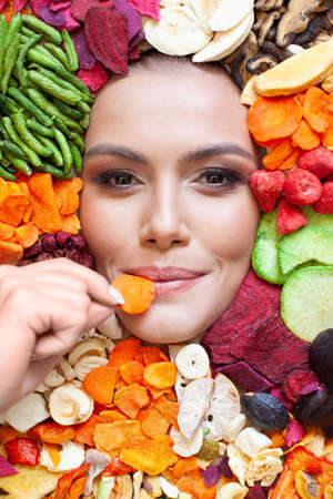 Happy woman eating carrots chips on fruits and vegetables chips, healthy eating and diet concept 免版税图像