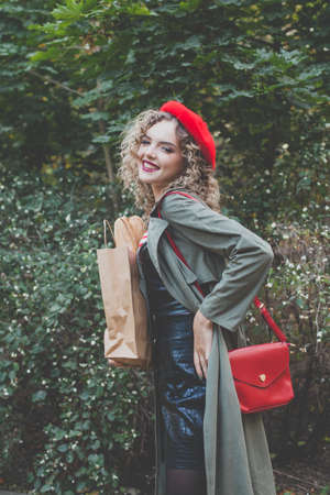 Beautiful young woman with curly hair wearing red french beret and handbag outdoor