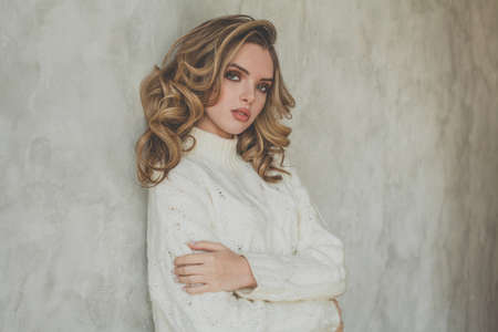 Pretty young blonde woman with healthy curly hairstyle wearing white pullover 免版税图像