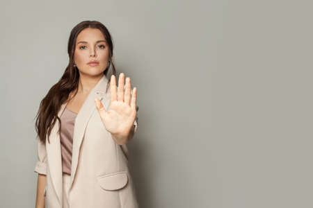Clever business woman showing stop gesture
