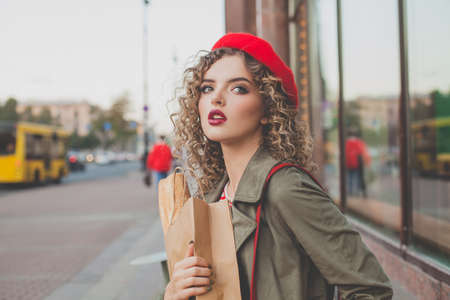Attractive young woman in red beret with fresh french baguette in craft paper bag outdoors
