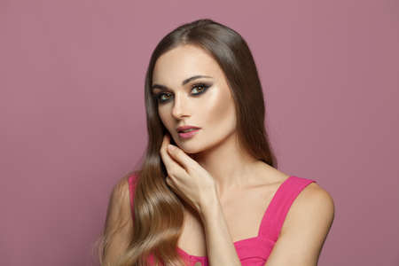 Stylish brunette woman with long healthy hair on pink background Stockfoto