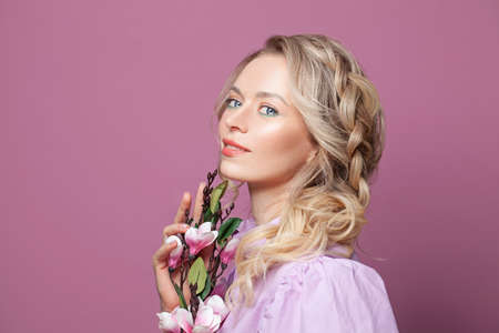 Beauty portrait of female face with natural skin. Attractive woman with makeup, blonde hair and flowers