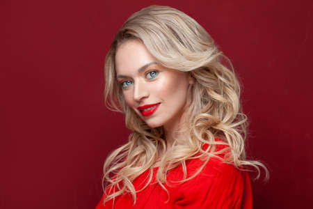 Cute model with perfect smile and beautiful face isolated on red. Nice blonde woman with make up portrait
