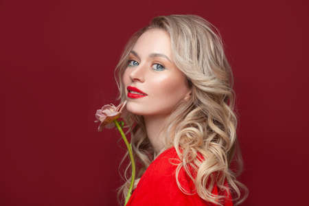 Summer beauty. Happy blonde woman with flower on red background