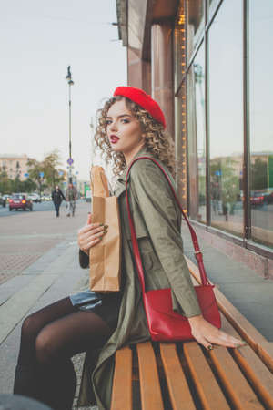 Young lady in red beret sitting outdoor Stockfoto