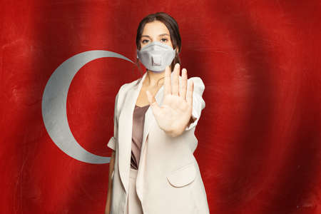 Prevention of virus disease in Turkey concept. Woman in anti virus protection mask showing stop gesture on Turkish flag background