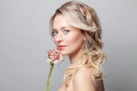 Beautiful young woman with clean fresh skin touch her face flower. Facial treatment. Cosmetology, beauty and spa