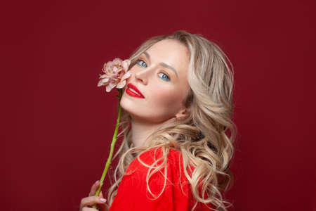 Confident blonde woman smiling on red background