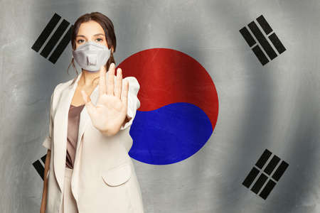 Smart woman in anti virus protection mask showing stop gesture on Korean flag background. Prevention of virus disease in South Korea concept. Stockfoto