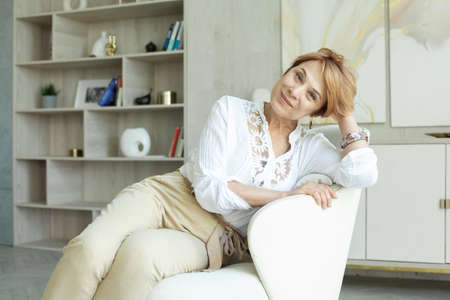 Elegant middle aged woman in white blouse resting at home
