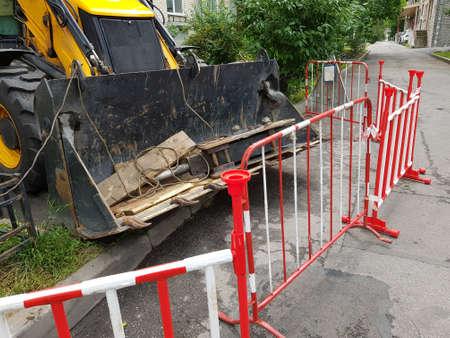 Construction industry concept. Excavator and hazard fence Stockfoto