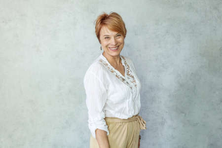 Successful smiling woman with toothy smile looking at camera