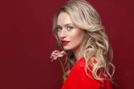 Stylish model woman with makeup and healthy curly hair on red background, beauty portrait