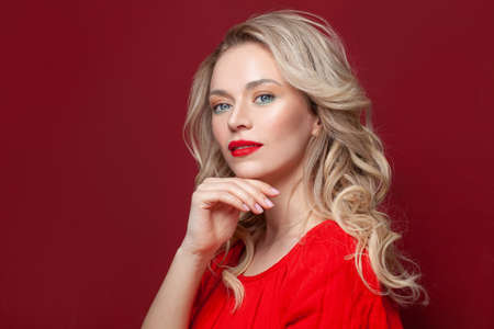 Beauty portrait of cute blond female face with natural skin on red Stockfoto