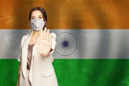 Indian woman in anti virus protection mask showing stop gesture on Indian flag background. Prevention of virus disease in India concept.