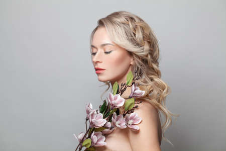 Healthy woman model with clean skin, light nude make-up, closed eyes and curly blonde hairstyle background