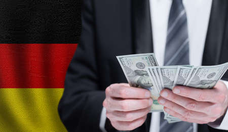 Money in male hands on German flag background. Banking, business, investment, corruption and social problems in Germany concept Stockfoto