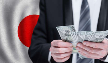 Dollars banknotes in male hands on Japanese flag background. Banking, business, investment, corruption and social problems in Japan concept Stockfoto