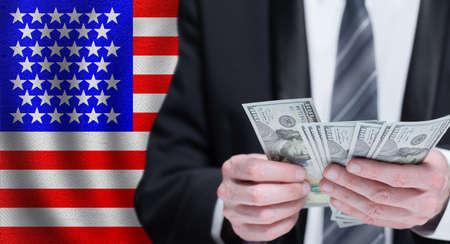 Dollars banknotes in male hands on National USA flag background
