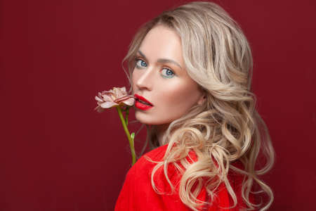 Pretty model woman with long curly hair on red background
