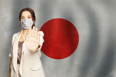 Prevention of virus in Japan concept. Woman in anti virus protection mask showing stop gesture on Japanese flag background Stockfoto